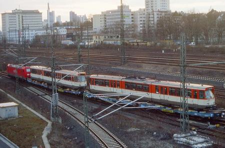 Rote DB-Lok zieht Flachwagen, die mit Straßenbahnwagen beladen sind