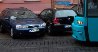 blauer Ford ragt ins Gleisbett und blockiert Straßenbahnen
