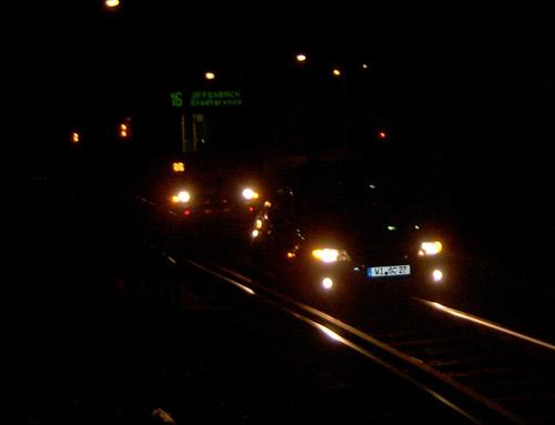 Nachtaufnahme eines ins Gleisbett gefahrenen Autos, dahinter eine wartende Straßenbahn