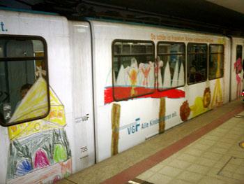 U-Bahn mit über Fensterflächen geklebten vergrößerten Kinderzeichnungen