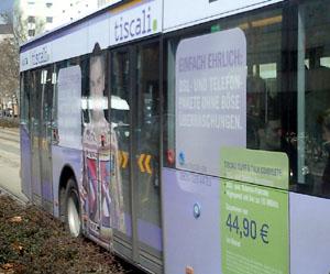 Türseite Stadtbus Frankfurt mit auf Fensterflächen aufgeklebten Werbetexten und Personenfotos