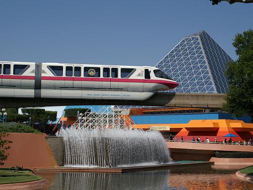 Disney-Monorailzug überquert in der Disneyworld Florida ein Becken mit Springbrunnen. Im Hintergrund ein pyramidenartiges Gebäude.