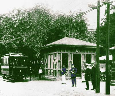 Straßenbahnwagen an der Endstelle Mathildenplatz mit alten Holzwartehaus, Personal und Passanten. Grün coloriertes Schwarzweiß-Bild