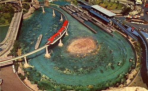 Ein roter Zug der Einschienenbahn fährt über den See von Disneyland Kalifornien. Im See sind mehrere U-Boote.