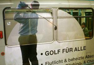 Golfspieler mit überdimensionalen Golfball, aufgeklebt über Fensterfläche eines Frankfurter U-Bahnwagen