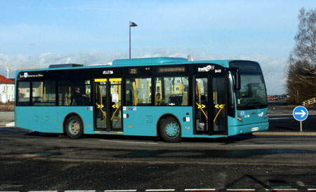 türkisblauer kurzer Stadtbus befährt Kreisverkehr am Frankfurter Riedberg