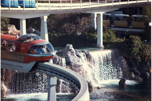 Ein roter Zug mit markanter Aussichtskanzel überquert einen See mit Wasserfall im Disneyland Kalifornien.