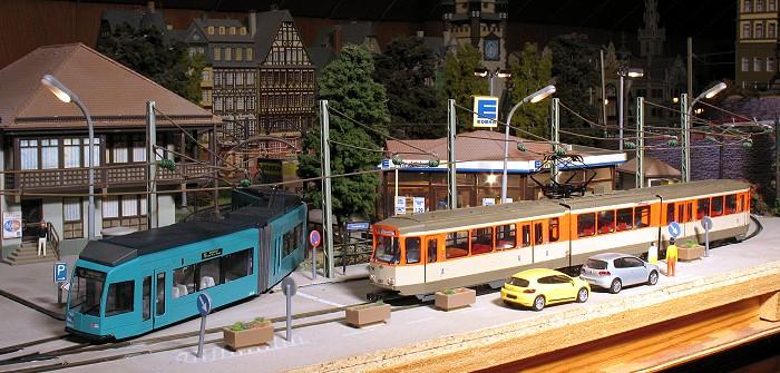 Modellstraßenbahnen Typ R und Pt in orange/hellelfenbein. In der Mitte der Schleife ein Supermarkt.