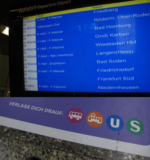 """DFI-Monitor an der S-Bahnstation Hauptwache - Alle Züge fahren """"In Kürze"""" - auf dem Boden davor Werbung """"Verlass dich drauf - Bus, Tram, U-Bahn und S-Bahn"""""""