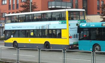 """Berliner Doppelbus auf Testeinsatz auf der Frankfurter Buslinie 34. Der gelbe Bus trägt die Werbeaufschrift """"Typisch Frankfurt immer hoch hinaus"""" und Abbildungen von Frankfurter Hochhäusern"""