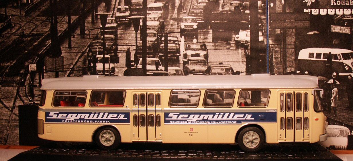 Seitenansicht eines Modellbusses Typ Büssing Senator mit Reklame für das Möbelhaus Segmüller, im Hintergrund Foto mit mehrspurigen Autoverkehr.